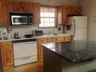 Fully equipped kitchen includes a stove, microwave, dishwasher, toaster oven and coffee maker.