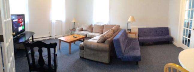 This grand first floor living room offers a TV, sectional,  two single futons and table for games.