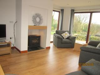 Lounge with floor to ceiling windows, underfloor heating and propane gas fired stove