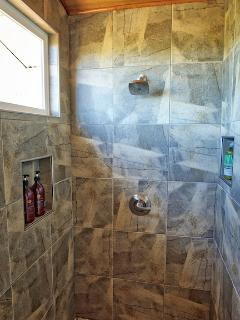 Bathroom also features an elegant tiled shower enclosure