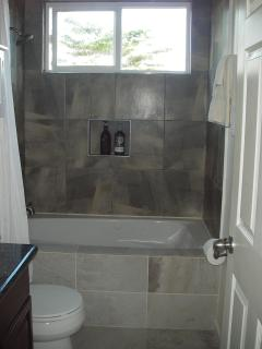 Second bathroom features a tiled bath enclosure with a Jacuzzi tub.
