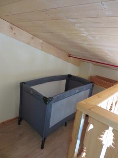 Mezzanine lounge with TV with chest of drawers and space for baby cot.