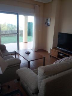 Detalle Salón con acceso al porche y al jardín privado. Dos sofás y gran TV 48´plana.