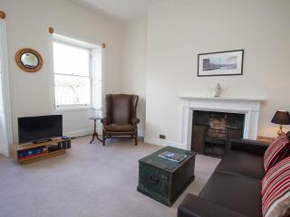 The living room - a large open space with leather sofa and period features.