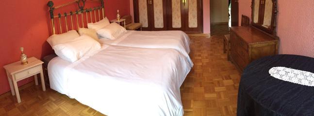 Habitación con dos camas y armario de cuatro cuerpos.