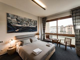 Bedroom with full wall window overlooking Arno river and Ponte Vecchio