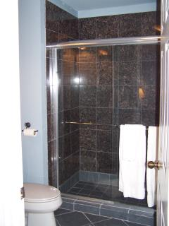 Two person granite shower with marble sink and designer towels.