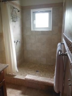 Both bathrooms have large tiled showers