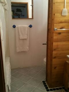 Bathroom. Toilet is behind the divider.  Shower/bathtub on the left, sink on the right. Towels incl