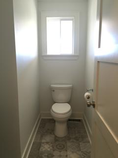 Main floor 1/2 bath located right of the entry features Italian porcelain tile and pedestal sink.