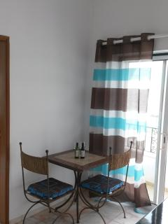 Dining table with 2 chairs and sliding doors to the balcony with 2 chairs