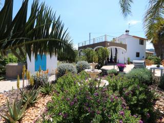 Omgeven door prachtige bloeiende tuin en palmen.