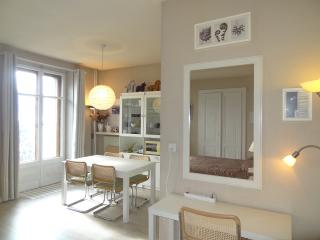 Desk/vanity toward dining area with tall French doors to balcony and views.