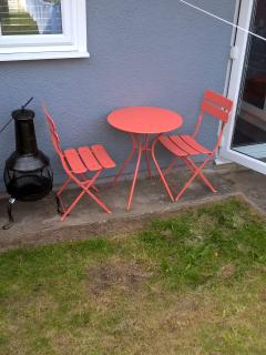 Small table and chairs with Chiminea in the enclosed back garden.