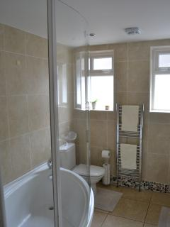 Bathroom with vanity unit, 2 basins, toilet with soft close lid, and large corner bath with shower.