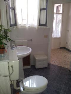 Bagno con: gabinetto, bidet, doccia, lavatrice e biancheria da bagno.