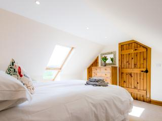 King size bedroom with full roof window overlooking countryside views.