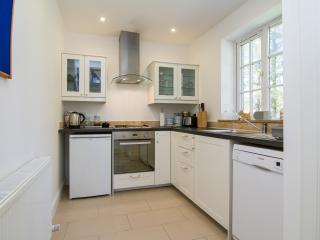 Kitchen with washing machine, dishwasher, electric hob, extractor hood.