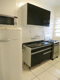 Cozinha equipada com louças e panelas. Cafeteira, torradeira, liquidificador, fogão e microondas
