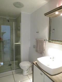 Banheiro com chuveiro a gás e água quente na torneira da pia