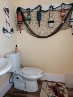 1/2 bath off of kitchen w/ beach motif and large window w/ custom shade.