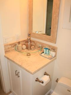 Guest bathroom- glass vessel  sink,  natural stone vanity top