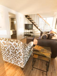 Living room w/comfortable seating, TV with cable and DVD player, stairs to 2nd floor. ©2017