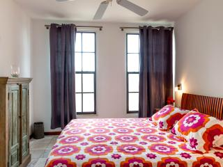 Air-conditioned bedroom with ceiling fan and mosquito screens as well.