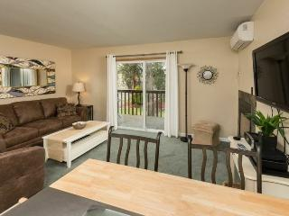Cozy and bright living room with fireplace and balcony overlooking park like grounds.