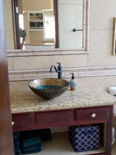 Unique tiled bathroom, glass bowl sink, island wood cabinet with granite top