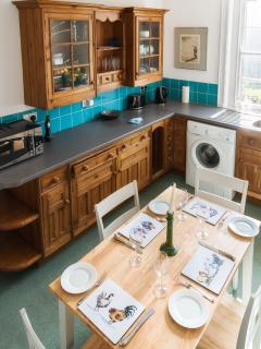 Fully equipped kitchen with washing machine and table and chairs to seat 4 people.