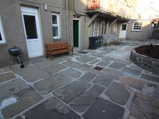 Back Garden / Patio area with BBQ and bench. South facing sun trap!