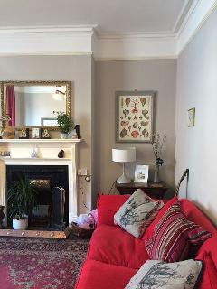 Comfortable living room with large sofas, armchairs, tv and plenty of original features and art