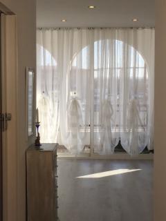 sala con grande ventana acristalada con alcon vistas al mar