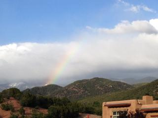 Rainbow over hiking trails, facing Santa Fe ski area in the background.