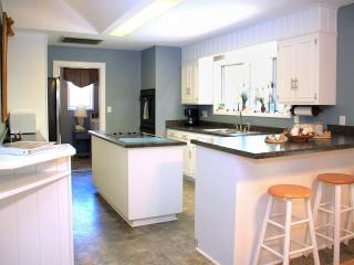 Large Kitchen with double ovens, smooth top stove, bar, and attached dining.