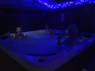 Guests enjoying the hot tub in the evening