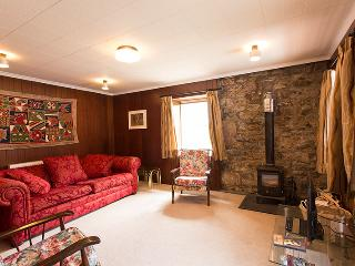 The cozy sitting room features wood panelling and stone with a multi-fuel stove..