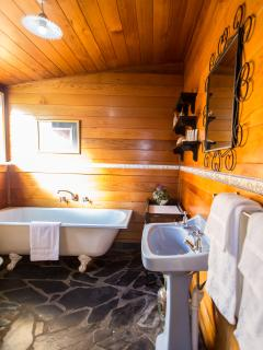 Cedar lined bathroom with claw foot bath - Queen Bee Cottage