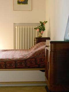 The bedroom is bright and spacious with doors directly to the terrace.