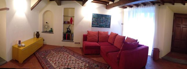 Ingresso casa dal piano terra, salotto con ampio divano, con televisore 40', stufa antica 'Felici'
