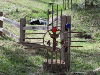 Angel sign along split rail fence marking the driveway with cedar creek waterfall in the background