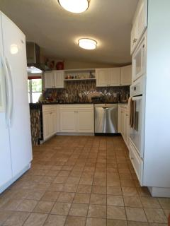 Kitchen area with large oven, cooktop, double door refuge & microwave appliances, and all utensils