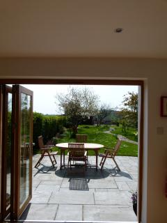 Open bi-fold doors from dining area to garden.