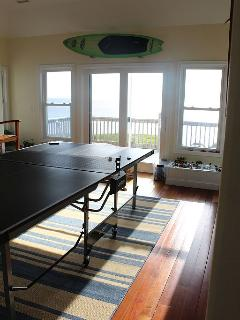 Top floor game room with a flat screen TV, wet bar, wine fridge and sunset sound side deck.