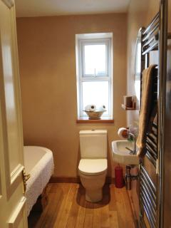 bathroom with roll top deep bath