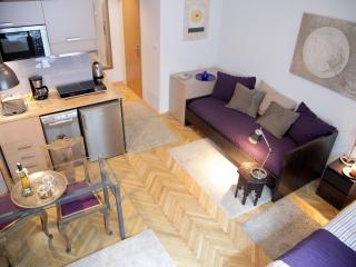 it features an open-plan layout, including a sleeping area with two single beds and flat-screen TV
