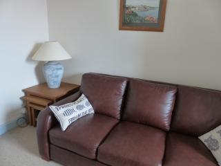 With little seaside touches,  living room is furnished with leather settees and oak tables.