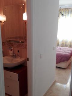 Pasillo de acceso dormitorio 1, con vista de baño y cama