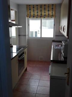 Vista de la cocina, con vitroceramica, lavavajillas, horno y microondas